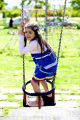 Bambina felice sull'altalena al parco giochi