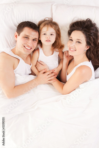 Happy family, mother, father and daughter resting on the white b