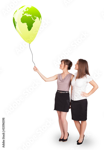 Happy ladies holding a green globe balloon