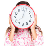 Child in pajamas wearing a clock in place of her face