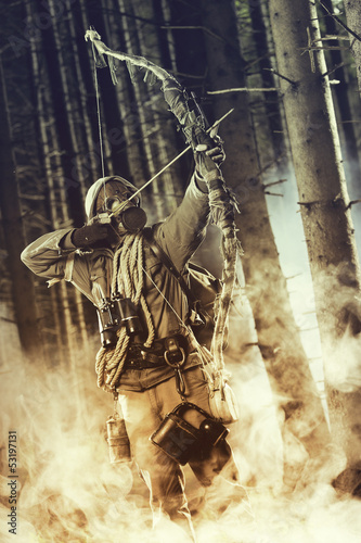 A male bow hunter wearing gas mask