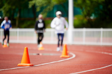 Running track at stadium with runners, focus on cone