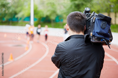 Cameraman shoots running races, view from back