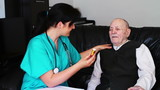 Nurse giving pills to a senior man