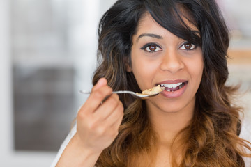 Woman holding a spoon with cereal