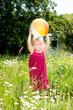 Kleines Mädchen mit Ball auf einer Sommerwiese