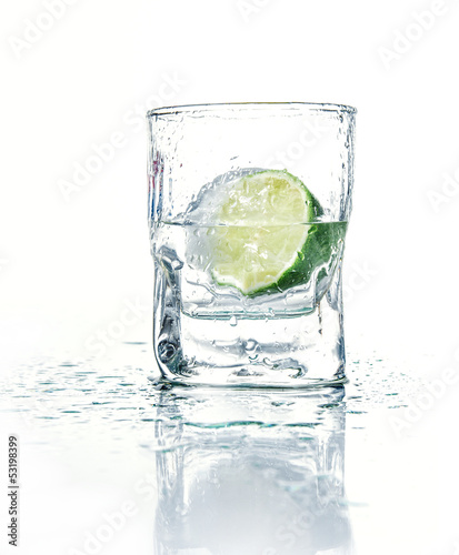 Vodka with lime in glass beaker, isolated on white