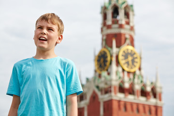 Portrait of boy in blue t-shirt against Spassky tower of Moscow