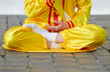 Lower part of woman body wearing clothes, sitting in lotuы