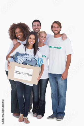 Happy group of volunteers holding donation box