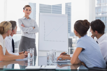 Businesswoman with arms folded in front of a growing chart
