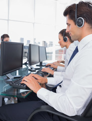 Group of call center employees working on computers