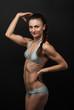 Young fitness woman in bikini flexing bicep