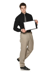 Young serious businessman showing blank clipboard