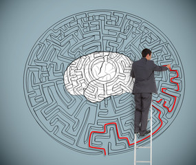 Businessman trying to solve a large maze with a brain illustrati