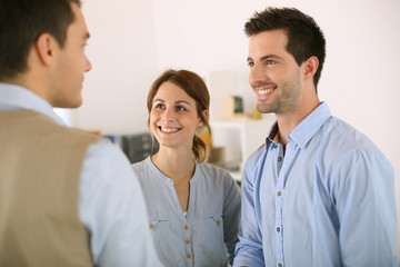 Cheerful couple shaking hand to salesman