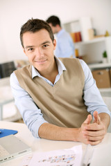 Smiling man sitting at desk in office