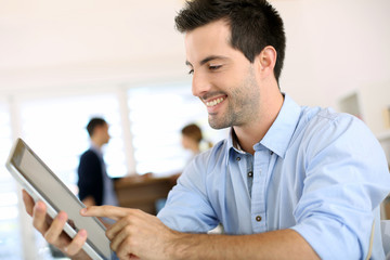 Smiling man in office working on digital tablet