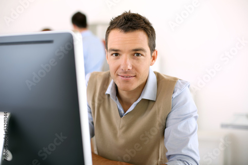 Man working in office in front of desktop computer