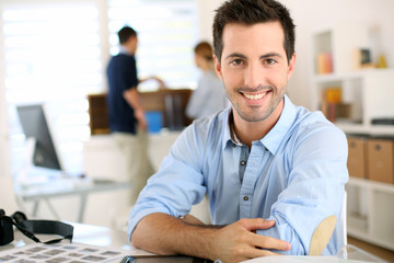 Portrait of cheerful man sitting in office