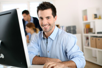 Man in office working on desktop computer