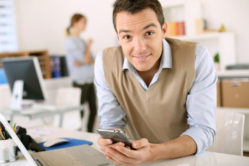 Man in office sending message with smartphone