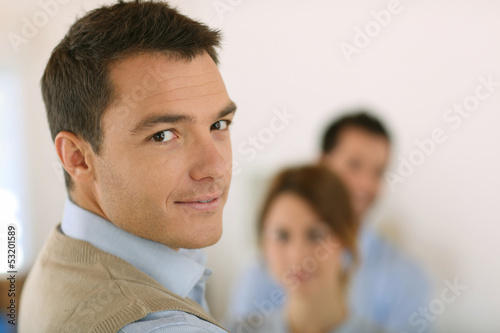 Handsome man standing in front of business team