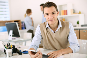 Handsome guy working with tablet in office