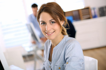 Portrait of cheerful girl in office