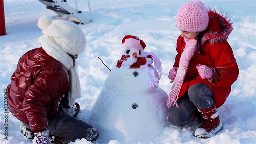 Happy girls playing a game in front of  snowman