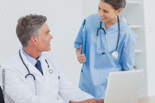 Doctor with a clipboard talking to a colleague