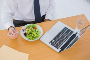 Overhead of a businessman eating a salad on his desk
