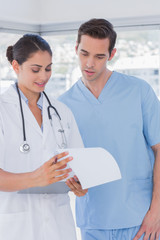 Doctor and surgeon reading over notes on clipboard