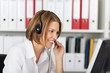 Serious smiling businesswoman talking on headset
