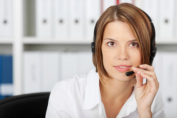 Confident businesswoman talking on headset