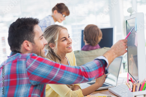 Designer pointing at the screen of a colleague