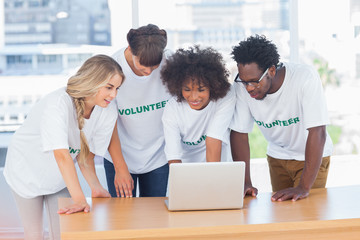 Volunteers working together on a laptop
