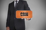 Businessman touching orange tag with the word crm written on it