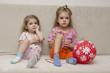 Две маленькие девочки сидят на диване с шариком