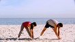 Sportsman and sportswoman stretching on the beach
