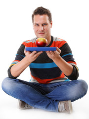 Man holding a book and one red apple full body