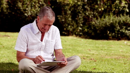 Mature man sat on the grass using his tablet computer