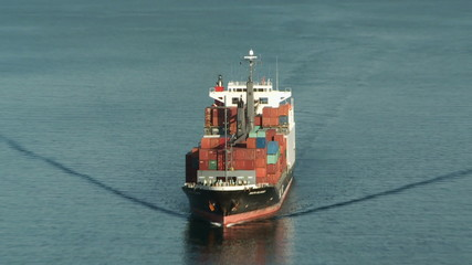 A large cargo ship is on the blue sea on the camera. Zoom camera