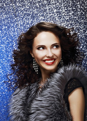 Fashion Model with Shiny Earrings in Fur Vest. Toothy Smile