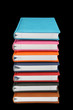 Stack of colorful books on black background