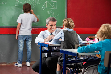 Teacher Looking At Schoolgirl While Crouching At Desk