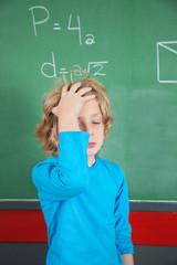 Sad Schoolboy Standing By Board In Classroom