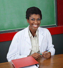 Confident Female Professor Sitting At Desk