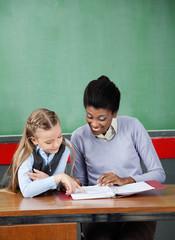 Schoolgirl Pointing In Binder With Teacher At Desk