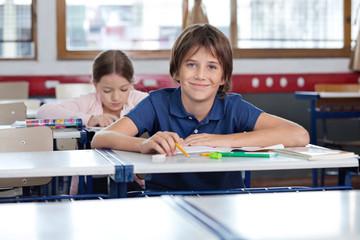 Cute Schoolboy Sitting In Classroom
